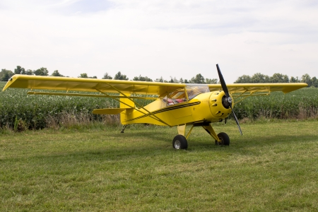 fixed wing aircraft: Single engine fixed wing aeroplane parked on a green grass field on display during a rural airshow