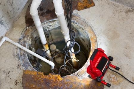 bomba de agua: La reparaci�n de una bomba de sumidero en un s�tano con un LED rojo de luz que ilumina el pozo y tubos para el drenaje de las aguas subterr�neas