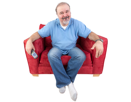 men socks: Man sitting in a comfortable armchair with a remote control and a bored expression as he watches something on television that he has seen before