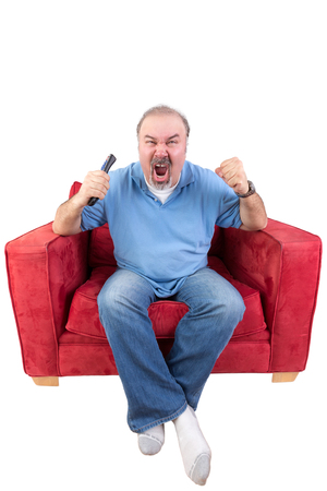 Middle-aged bearded man screaming at the television in anger or as he cheers on his favourite sports team while holding the remote control in his hand , isolated on white Reklamní fotografie