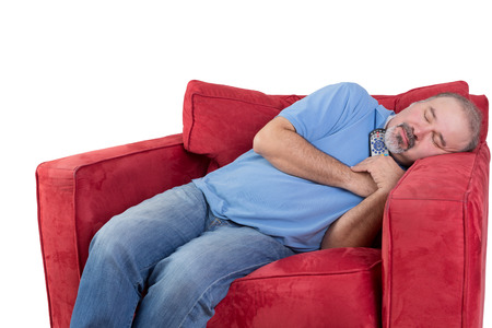 possessive: Tired middle-aged man fallen asleep while watching television with the remote control in his hand and his head resting on the arm of a comfortable red chair, isolated on white