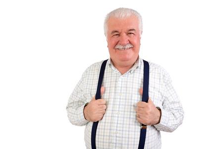 bigote: Hombre de pelo gris mayor confidente con un bigote y radiante sonrisa amistosa sosteniendo sus tirantes o tirantes, parte superior del cuerpo aislado en blanco