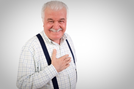 sincere: Sincere senior man with his hand on his heart looking at the camera with a warm friendly smile, upper body studio portrait on grey with copyspace Stock Photo