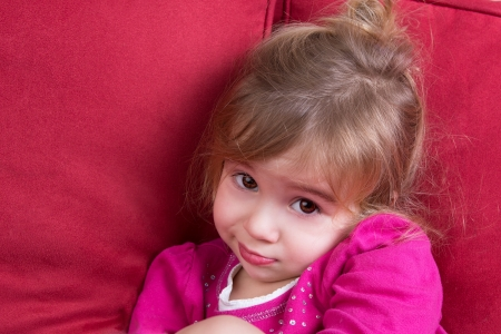 shyness: Shy little girl looking at the camera with big eyes as she snuggles down in a comfortable armchair
