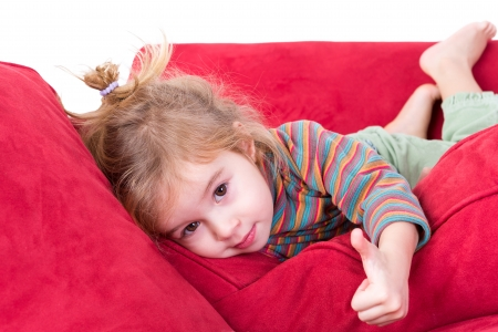 Beautiful little girl giving a thumbs up gesture as she lies comfortably on her stomach on a red couch looking at the camera with a friendly smile