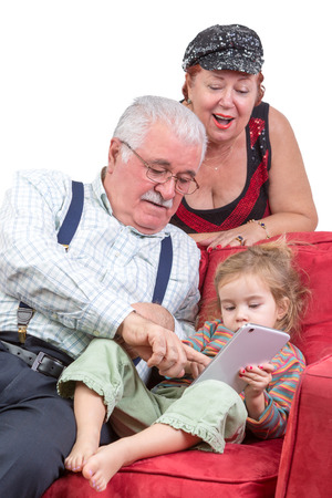 Grandparents babysitting their granddaughter sitting together ion a couch pointing out information on the tablet computer to her as they enjoy an e-book together photo