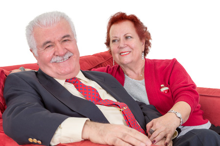 devoted: Devoted senior couple seated on a red sofa holding hands with the wife looking lovingly at her husband as he gives the camera a beaming smile Stock Photo