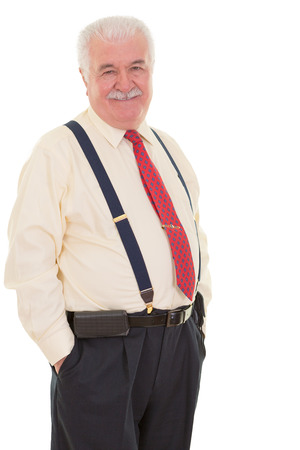 executive affable: Genial senior businessman in braces standing in a confident relaxed pose with his hands in his pocket smiling at the camera, three quarter isolated on white