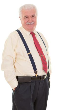 Genial senior zakenman in accolades staan in een zelfverzekerde ontspannen houding met zijn handen in zijn zak lachend naar de camera, drie kwart op wit wordt geïsoleerd