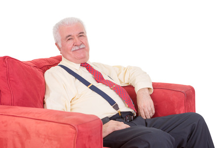 mellow: Senior grey-haired gentleman with a moustache wearing braces relaxing in a comfortable red armchair on a white background
