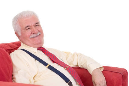affable: Jovial grey-haired senior man with a moustache relaxing in a comfortable armchair looking at the camera with a lovely beaming smile Stock Photo