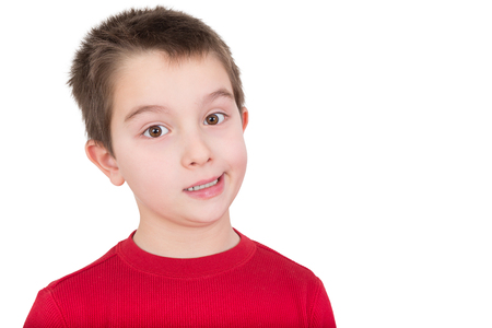 reacting: Skeptical young boy reacting in disbelief smiling ruefully and raising an eyebrow, isolated on white