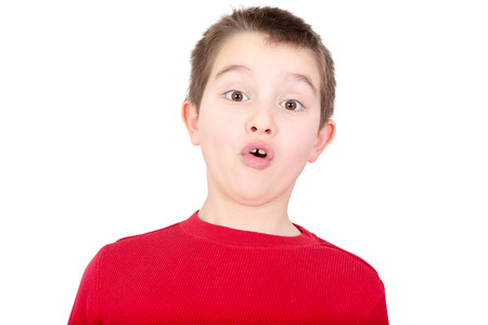reacting: Young boy reacting with a look of amazement and awe as he stares wide eyed at the camera with his mouth forming on oh, isolated on white
