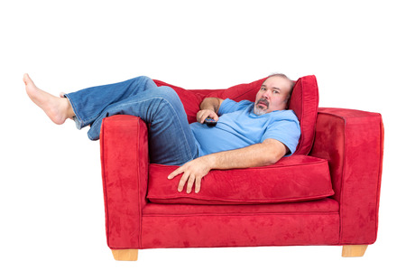 Man engrossed in watching television lying barefoot on a red couch with the remote control in his hand and a look of fascinated concentration, isolated on white