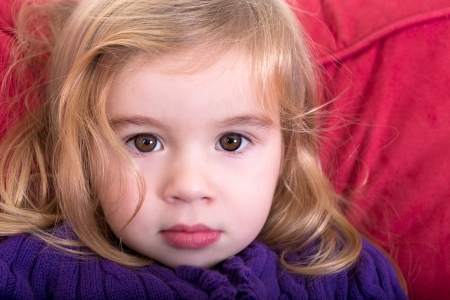 inscrutable: Close up facial portrait of a beautiful innocent young blond girl with a solemn wide eyed expression staring into the camera Stock Photo