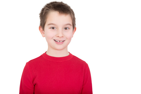 Young boy in a red t-shirt with a happy grin and alert expression, isolated on white