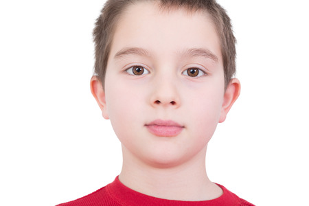 unemotional: Handsome young boy with a serious thoughtful expression and wide sincere eyes looking directly into the camera, close up facial portrait isolated on white