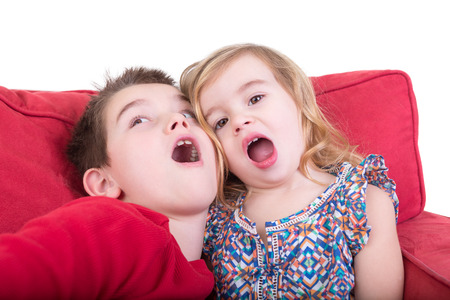 copycat: Two playful young children pulling faces as an attractive brother and sister sit together on a red couch playing copycat with their mouths wide open Stock Photo