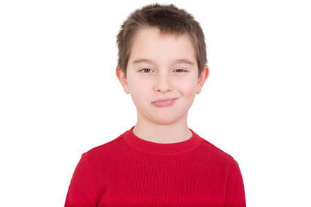 rueful: Skeptical young boy with a disbelieving expression looking thoughtfully at the camera as he assesses the situation, isolated on white