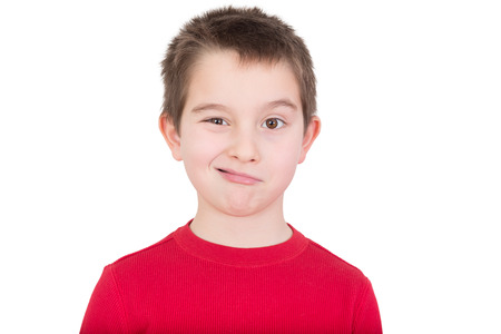 rueful: Cute playful young boy in a colourful red t-shirt standing winking at the camera, head and shoulders portrait isolated on white