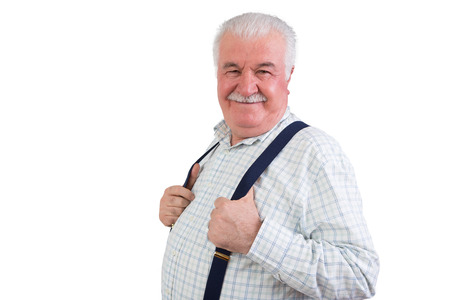 Jovial confident elderly man with a moustache and his hands hooked through his suspenders beaming happily at the camera, upper body isolated on white