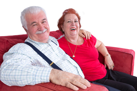 Joyful relaxed elderly couple sitting arm in arm on a red sofa laughing at the camera over white 版權商用圖片