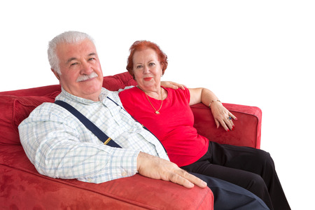 Attractive elderly couple smiling in satisfaction as they sit arm in arm on a comfortable red sofa over a white background