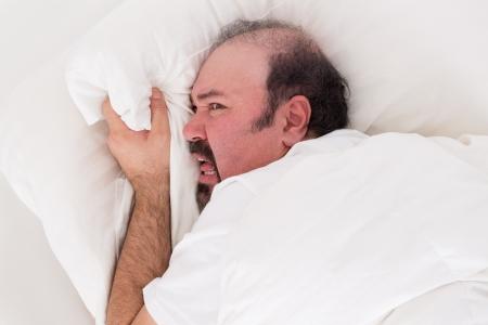 desperate: Insomniac aferrándose a la almohada en la desesperación mientras él torvamente se niega a levantarse por la mañana después de una noche de insomnio