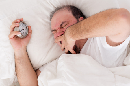 awoken: Man lying in bed yawning as he tries to wake up with his alarm clock clutched in his hand Stock Photo
