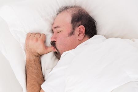 수염 남자의 근접 촬영은 고요한 결백 한 표정으로 잠자는 동안 큰 아기처럼 자신의 손가락을 빠는 그의 베개에 안고
