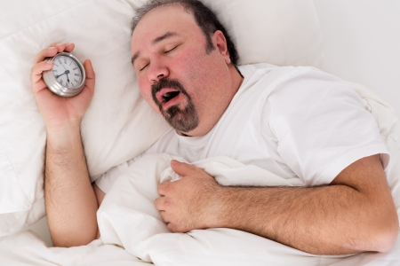 get tired: Lethargic tired man lying in bed yawning as he struggles to wake up unmotivated to start the new day and content to rather continue lying in bed as he holds his alarm clock in his hand