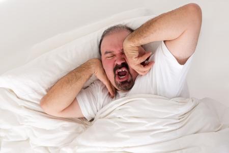 sono: Cansado homem deitado na cama estica e que boceja em um esfor