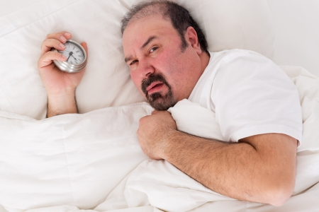 awoken: Irascible man glaring balefully at the camera as he lies in bed holding the alarm clock in his hand after a sleepless night wanting to remain in bed until noon Stock Photo