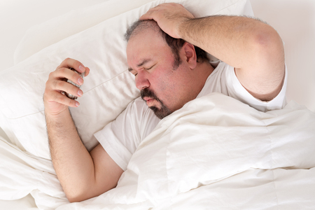 overwrought: Man suffering from a hangover clutching his head in one hand and alarm clock in the other as he suffers in the morning wondering what happened