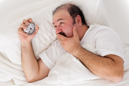 delaying: Man suffering from insomnia trying to sleep checking the time on his alarm clock in desperation as he realises he will not wake up in time for work if he sleeps now Stock Photo