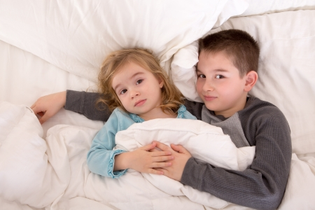 Affectionate little brother and sister lying in bed cuddling together under the duvet looking up sleepily at the camera photo