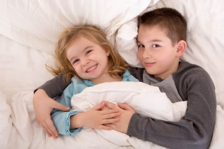 Mischievous young brother and sister in bed grinning up at the camera as they lie side by side under the duvet preparing to go to sleep photo