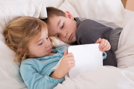 Cute little girl and boy reading a bedtime story as they lie together in bed looking at a tablet computer as they prepare to go to sleep with the little sister holding the notebook Stock Photo