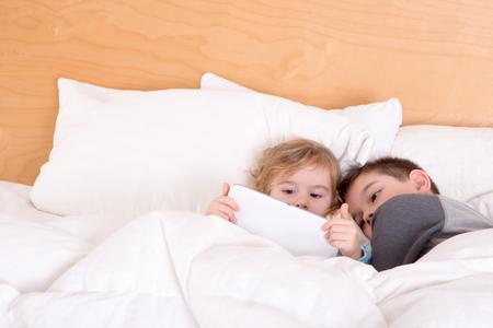 Broertje en zusje knuffelen samen slapen gaan onder een warme dekbed als ze een e-boek te lezen of surfen op het internet op een tablet-pc Stockfoto