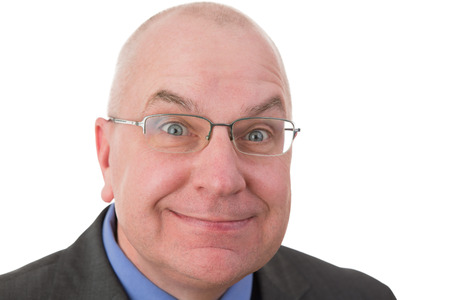Zealous businessman with a fanatical expression grinning at the camera with his eyes opened wide in expectation that the viewer will agree with him, head and shoulders portrait on white Stock Photo