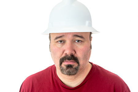 Morose glum looking man with a goatee beard wearing a hardhat looking at the camera with lacklustre eyes and a depressed expression, isolated on white
