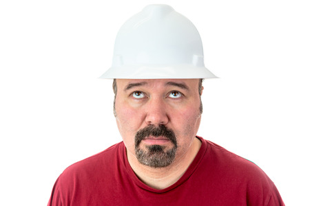 Glum looking workman wearing a hardhat looking for inspiration raising his eyes to the heavens in supplication, isolated on white Stock Photo