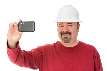 Smiling workman with a goatee beard wearing a hardhat taking a self-portrait using his smartphone, isolated on white