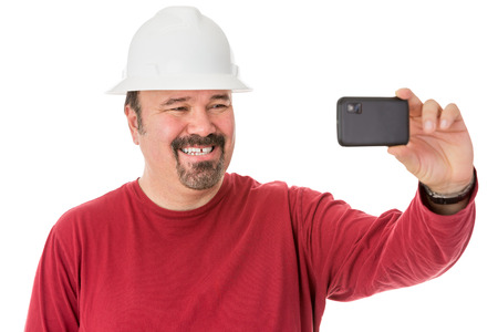 Workman with a neat goatee beard weaning a hardhat posing for a self-portrait giving a cheesy grin as he looks into the camera on his mobile phone, isolated on white photo