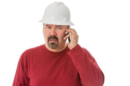 Workman with a goatee beard wearing a hardhat listening to a call on his mobile phone with a look of shocked confusion isolated on white photo