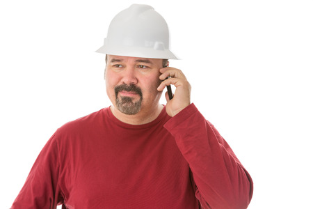 wry: Bored looking workman, engineer or architect chatting on his mobile looking away with a thoughtful wry expression as he listens to the conversation, isolated on white Stock Photo