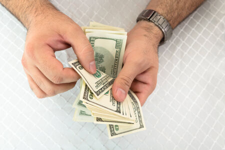 imposed: Close-up of a man hands counting dollar notes
