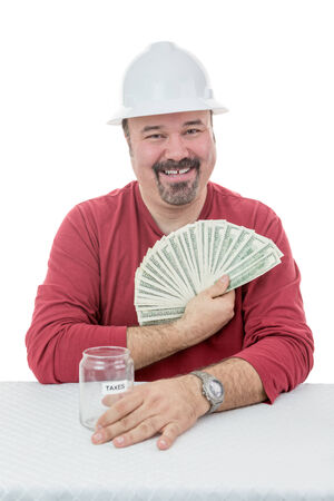 destined: Happy construction worker wearing a hard-hat holding-on to dollar notes destined to taxes Stock Photo