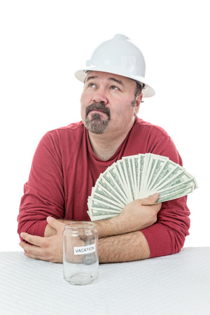 Unhappy construction worker holding-on to tax money and dreaming with what else he could do with it photo