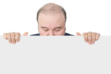 unemotional: Businessman holding a blank white sign suitable for advertising looking down with closed eyes and hiding his face behind the board in an effort not to have to issue an endorsement